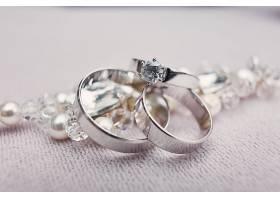 精致的白金银色结婚戒指放在水晶手镯上_371286501
