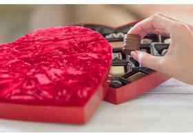 手拿着一盒心形巧克力的松露_1099802701