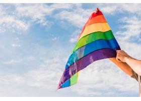 手持LGBT颜色和蓝天巨旗的男子_434148601