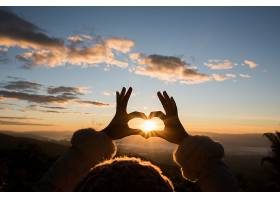 手的剪影与日出形成心形_392764101