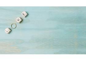 木质背景角上用立方体和结婚戒指制作的文字_493715901