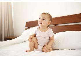 漂亮可爱的新生婴儿穿着粉色衬衫坐在家里的_902847201
