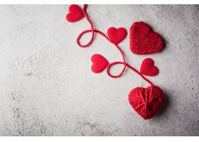 墙壁背景上的红色纱线心形_392837001
