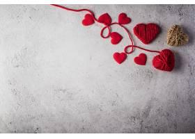 墙壁背景上的红色纱线心形_392837401