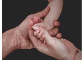 女人和男人牵着新生儿的手_1029205001