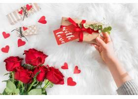 带礼品的手在羊毛床单上贴着装饰心和鲜花_363172401