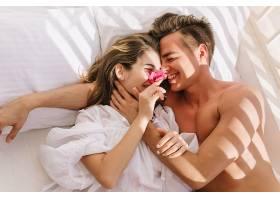欢快的年轻情侣躺在白色的床上在阳光明媚_1021625201