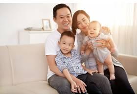 相爱的亚洲夫妇带着年幼的儿子和婴儿在家里_557732801