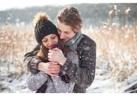 相爱的圣诞幸福情侣在雪域冬寒的森林里拥抱_927672601