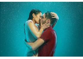 这对恩爱的情侣在青绿色的背景下在雨中接吻_1005517001