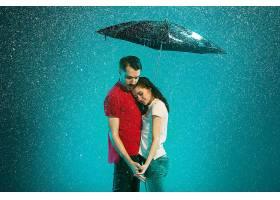 绿松石背景下撑着伞的雨中恩爱情侣_1005517501
