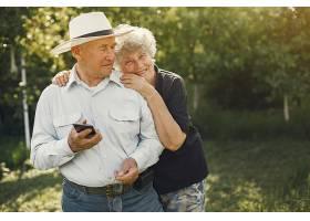 美丽的老夫妇在夏日花园里消磨时光_965951001