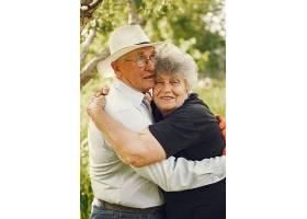 美丽的老夫妇在夏日花园里消磨时光_965957201
