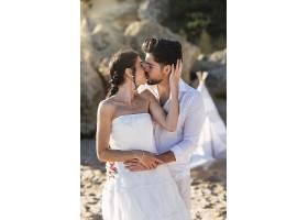 美丽的高加索夫妇在海滩上接吻_1169634501