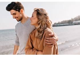 鼓舞人心的年轻男子在海滩散步时拥抱女友_1215289801