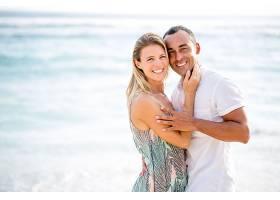 一对恩爱的情侣在夏日的海滩上拥抱_112197501