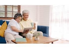 亚洲老年夫妇在家中的客厅里使用平板电脑和_439632501