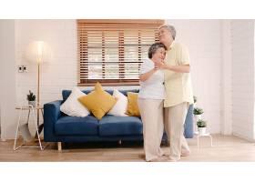 亚洲老年夫妇在家中起居室边跳舞边听音乐_439634101