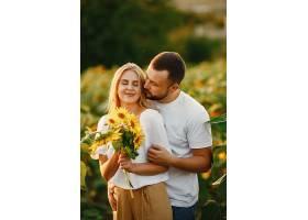 年轻恩爱的情侣在向日葵地里接吻夏日在野_1016478801
