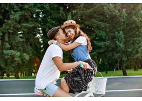 年轻情侣在森林背景的公路上骑自行车相爱的_1005619401