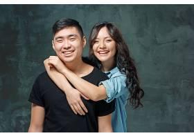 工作室灰色背景上微笑的韩国夫妇的肖像_1012918501