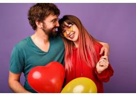 年轻可爱的潮人情侣在紫罗兰色的墙上摆姿势_985561401