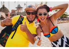 年轻漂亮的潮人情侣在热带海滩相爱用智能_1108349101