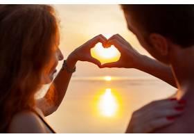 年轻的性感浪漫情侣在夏日海滩快乐地一起穿_1151446501