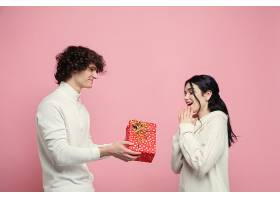 年轻美丽的情侣在粉红色的工作室墙上坠入爱_1264790501