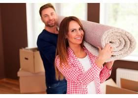 幸福夫妇为新家搬地毯的肖像_1110096701
