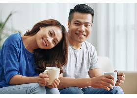 幸福的亚洲夫妇坐在家里的沙发上手里拿着_557742601