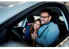 幸福的年轻夫妇享受着他们崭新的汽车_1113625501