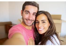 幸福的年轻夫妇在他们的新家自拍背景是纸_1107636501