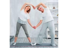 幸福的年长夫妇站在家里的瑜伽垫上_432144401