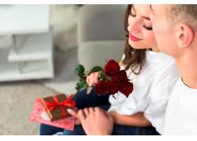 男子在沙发上拥抱手持红花的女子_356477001