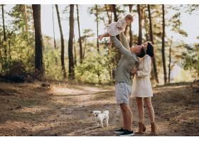 年轻的一家人带着可爱的小女儿在夕阳的森林_1029837201
