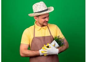 年轻的园丁穿着连体裤戴着帽子戴着工作_1243271901