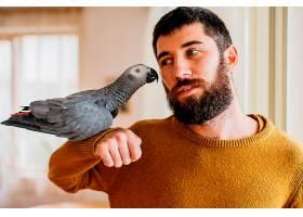 留胡子的男子抚摸可爱的小鸟_1089204601