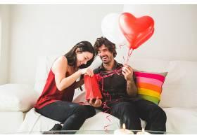年轻的女孩看着一个红色的包而她的男朋友_103465301