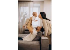 年轻的家庭带着蹒跚学步的女儿坐在家里的马_1230501901