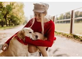 秋天公园里快乐的女人温柔地抱着她的狗_1201840001