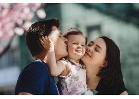 幸福的年轻父母带着一个小女儿站在外面盛开_291413001