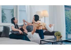 幸福的年轻的亚洲家庭一起在家里的沙发上玩_614250401