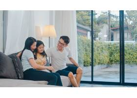 幸福的年轻的亚洲家庭一起在家里的沙发上玩_614250601