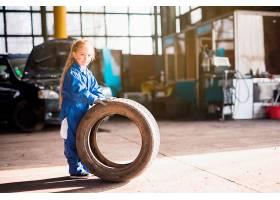 穿着整齐的小女孩站在汽车轮子上_420076201