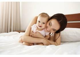 幸福美丽的母亲穿着睡衣躺在床上抱着她的_902847701