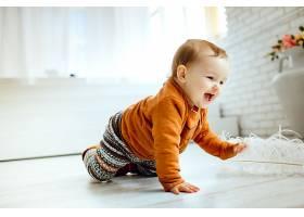 穿着橙色毛衣的快乐孩子在地板上玩羽毛_147155201