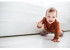 穿着橙色毛衣的快乐孩子在地板上玩羽毛_147155501