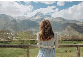 穿着礼服的新娘等着新郎看着雪峰林立的群_245492301