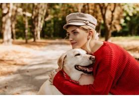 穿着红色毛衣的漂亮女孩在公园里可爱地抱着_1201844001